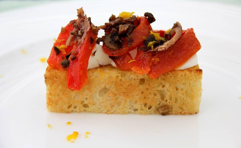 Pan-brioche alle olive con primosale marinato, acciughe, peperoni confit e olive secche